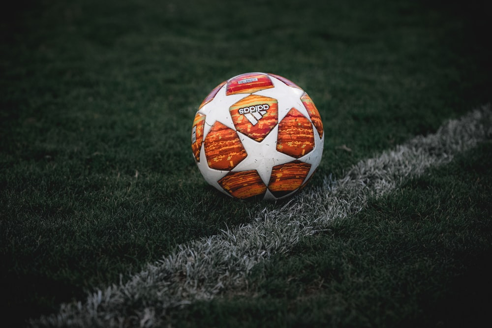 white and orange soccer ball on green grass field