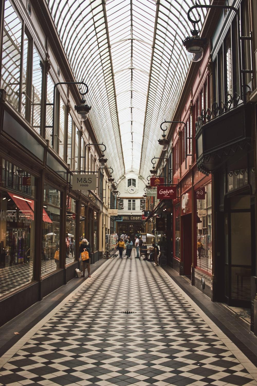 people walking on sidewalk in between buildings during daytime