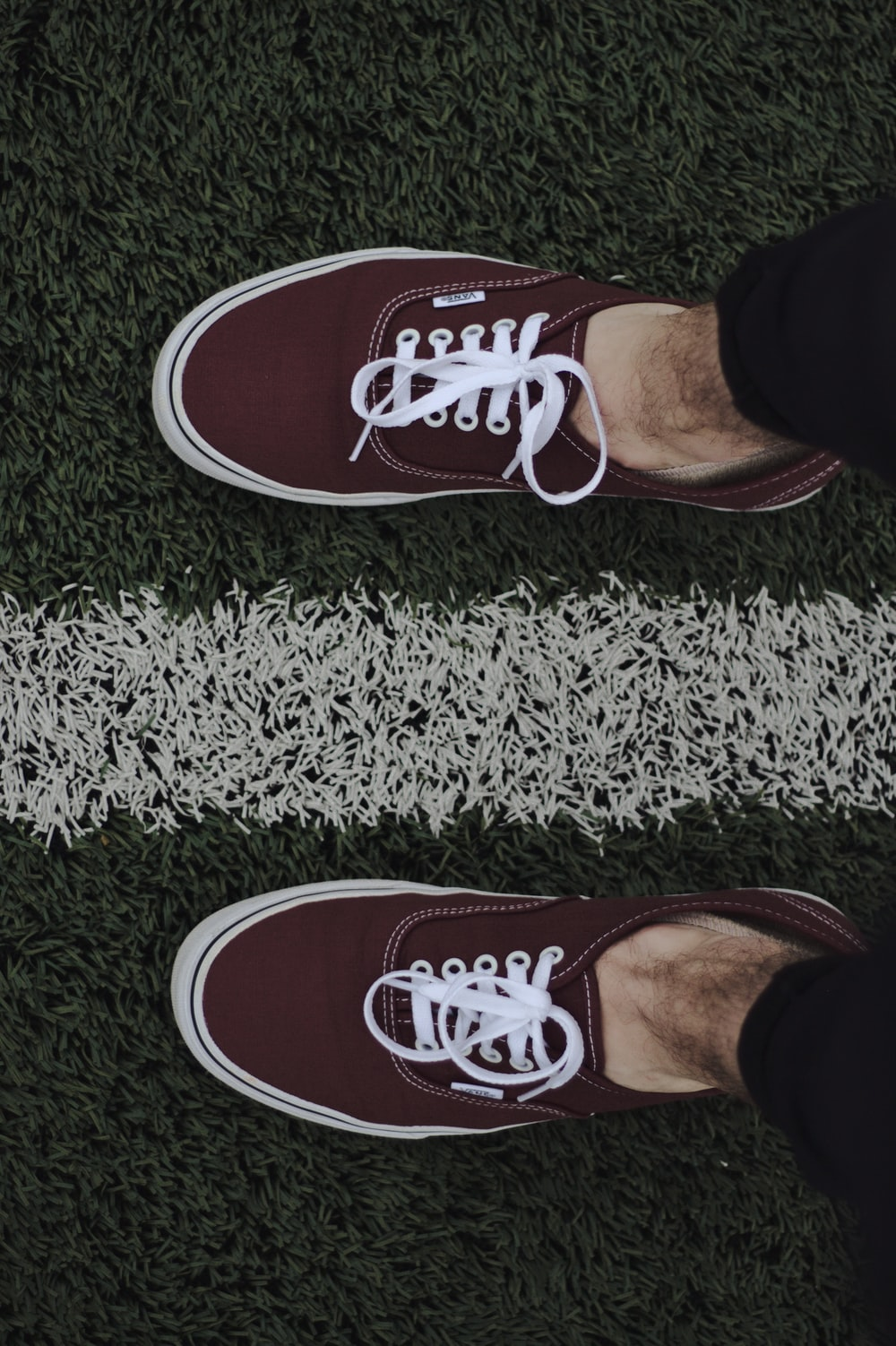 person wearing red and white vans low top sneakers