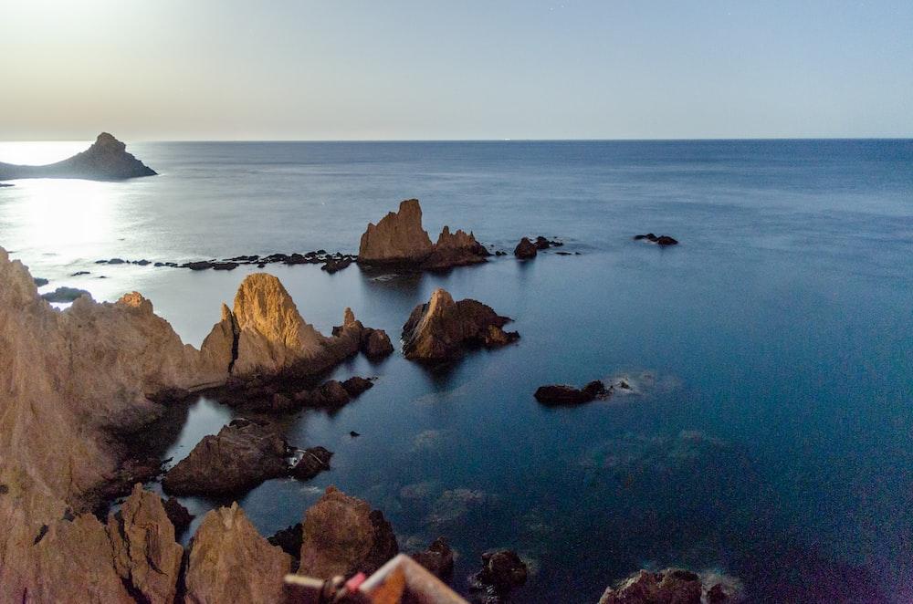 brown rocks on blue sea under white sky during daytime