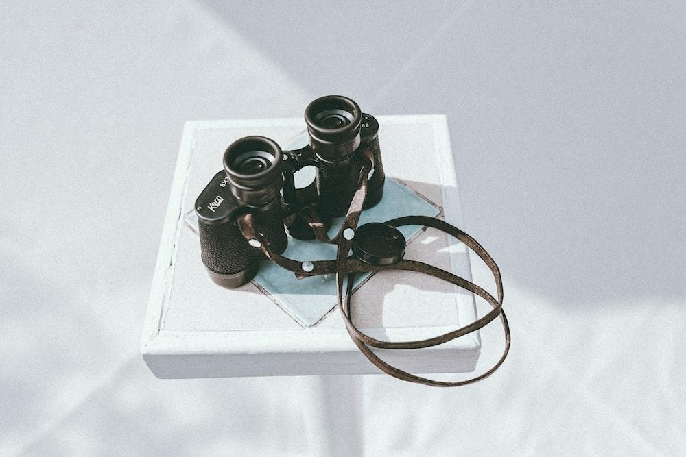 black binoculars on white table