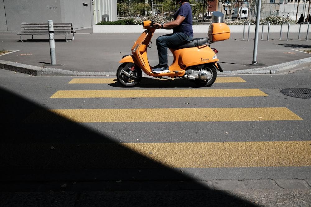 orange and black motor scooter parked on pedestrian lane during daytime