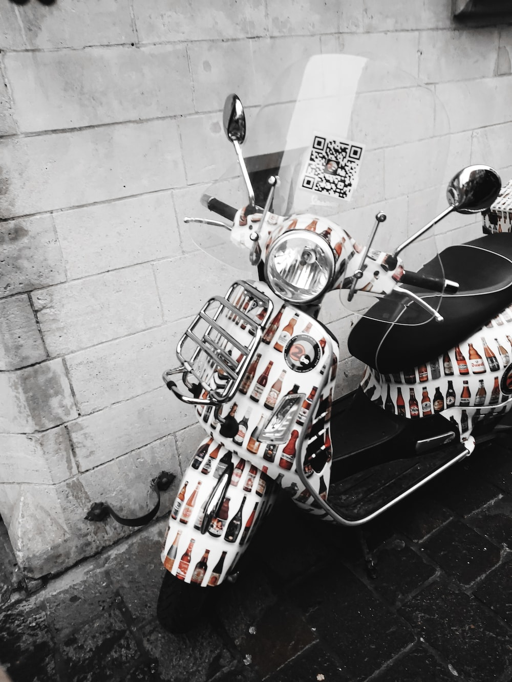 red and black motorcycle parked beside wall