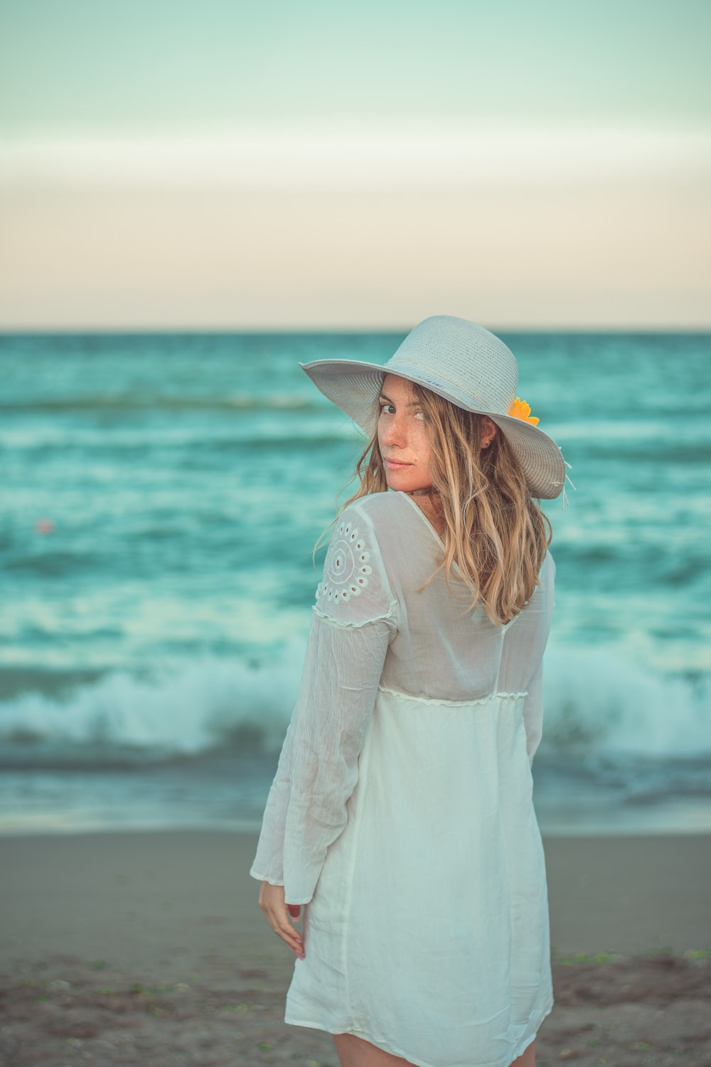 woman in white dress wearing brown hat standing on seashore during daytime
