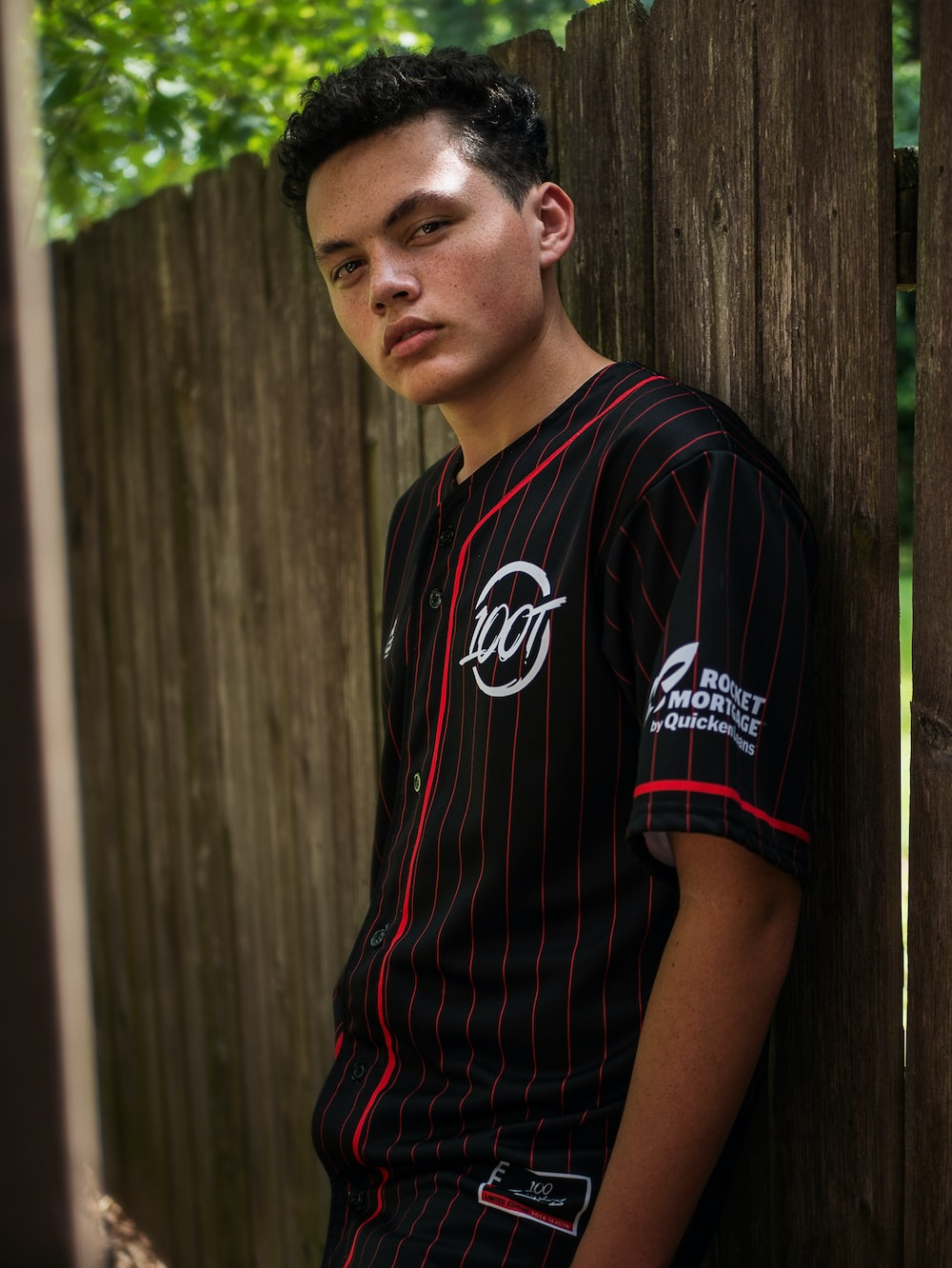 man in black and red crew neck t-shirt standing beside brown wooden fence