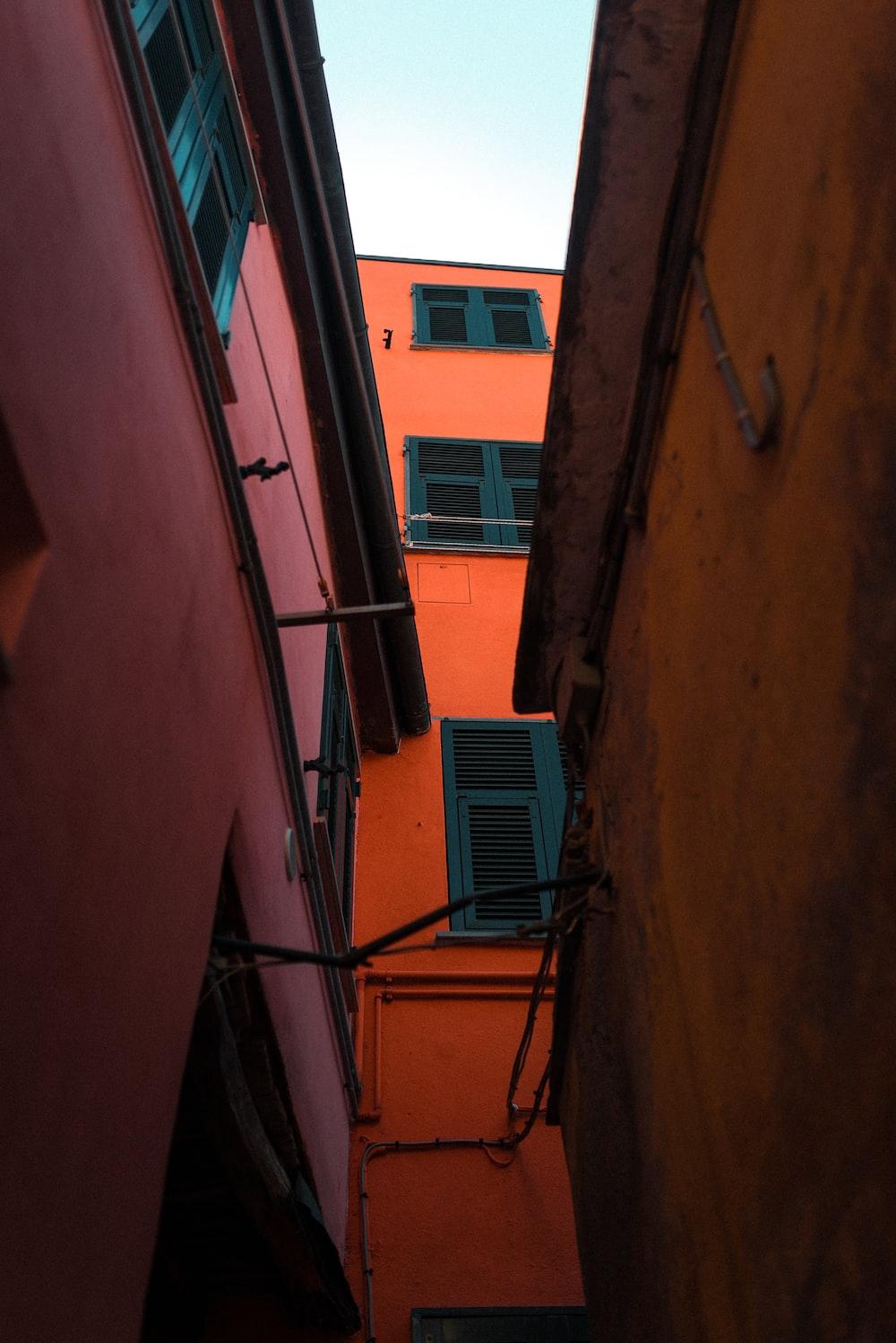 blue window type air conditioner on orange concrete building