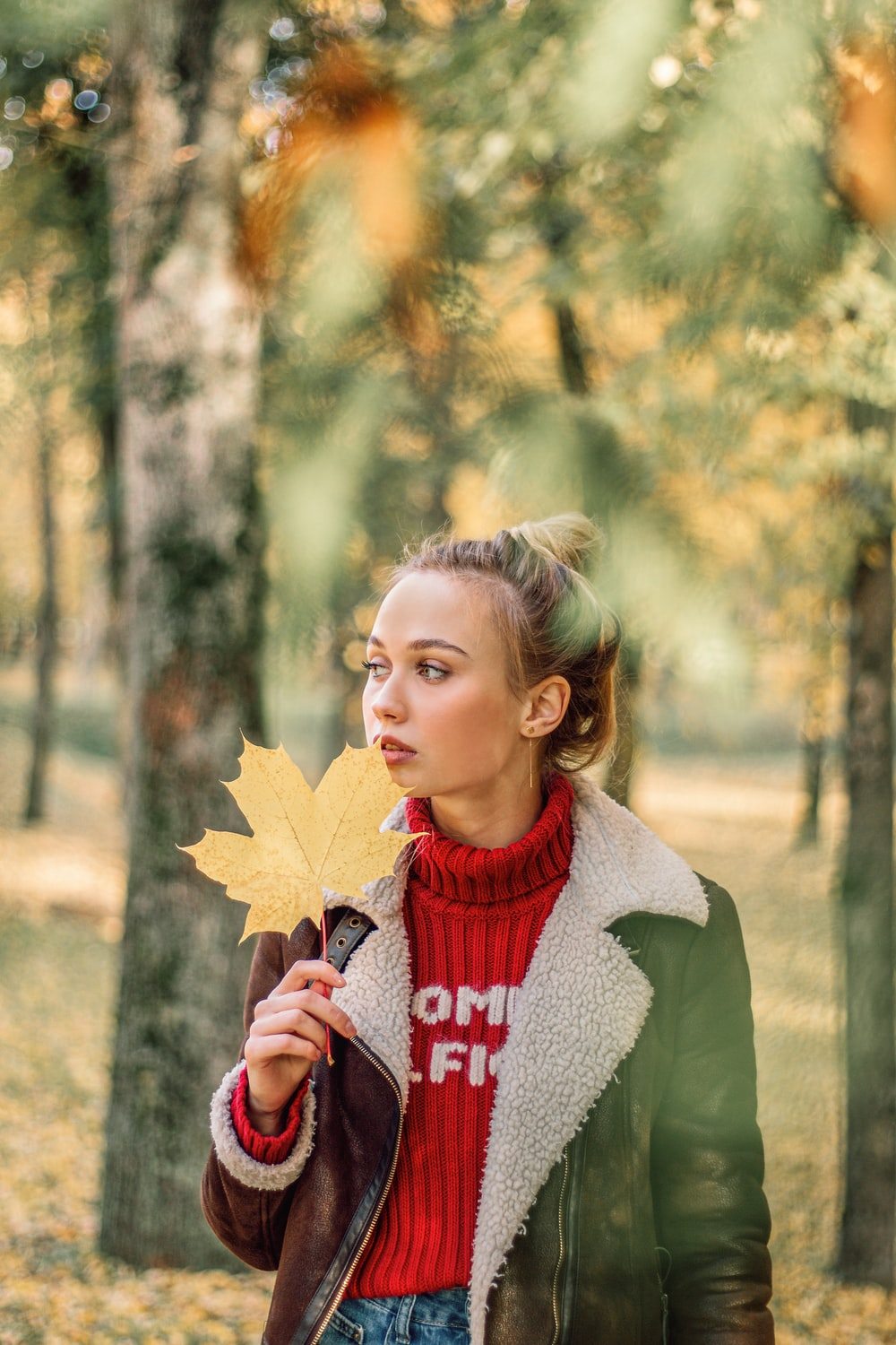 girl in green cardigan holding yellow maple leaf