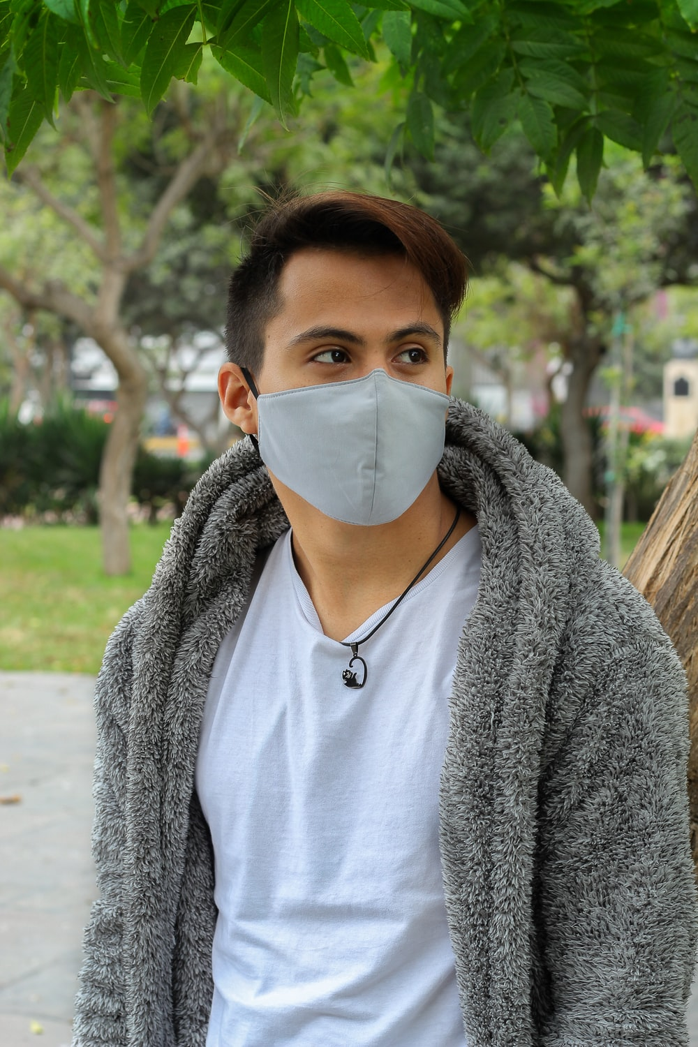 woman in gray cardigan wearing white face mask