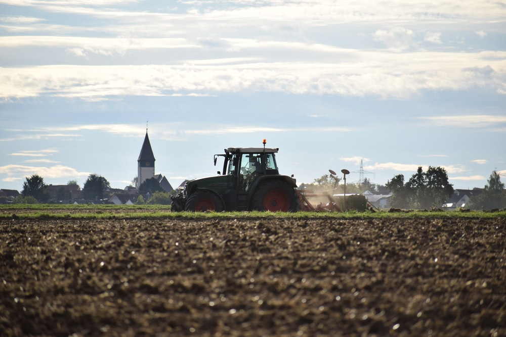 red tractor on brown field during daytime