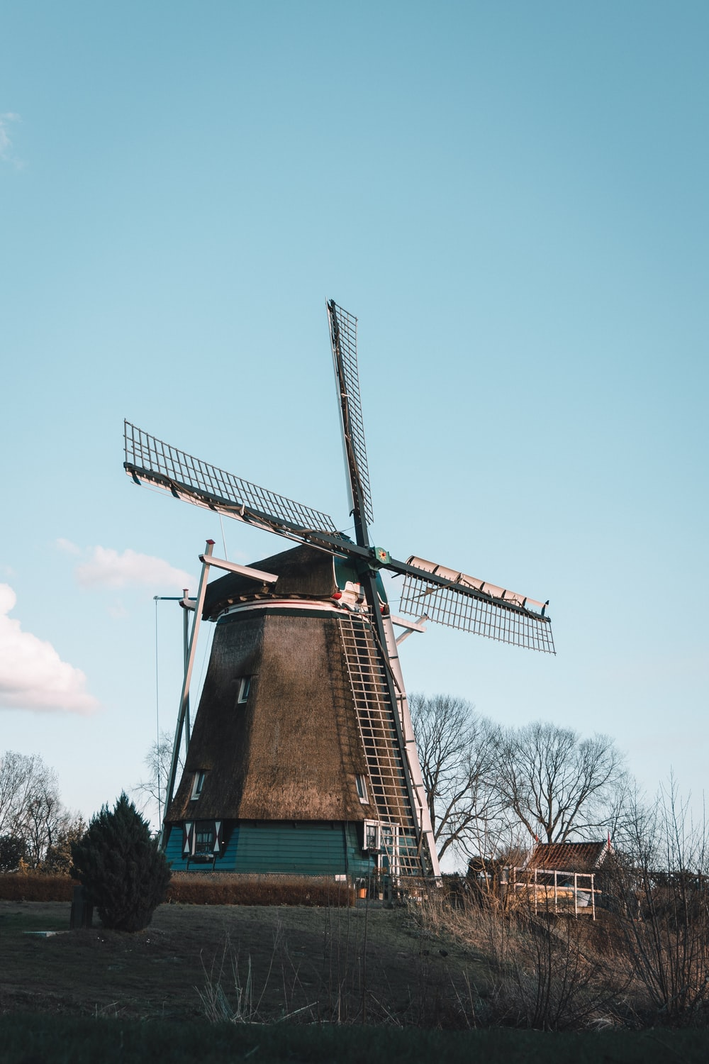 brown and green windmill under blue sky during daytime