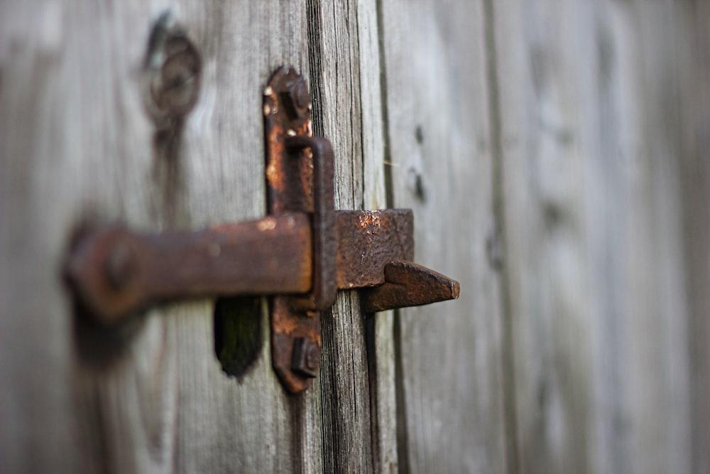 brown metal padlock on grey wooden fence