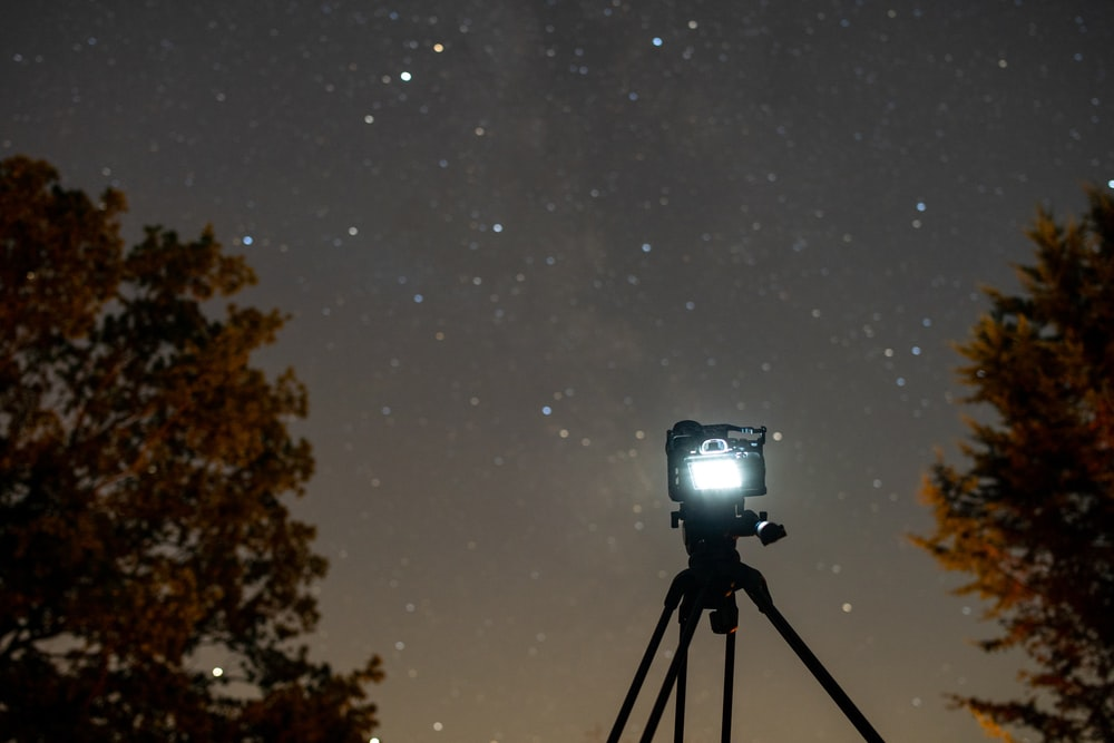 black camera with tripod during night time