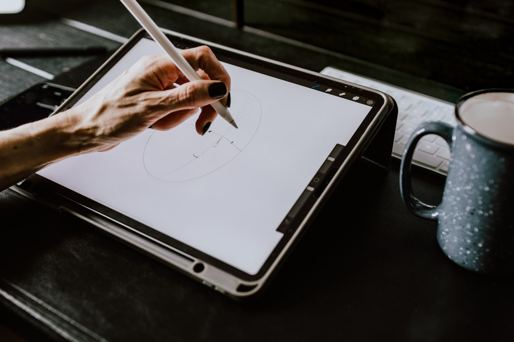 person holding white ipad with black case