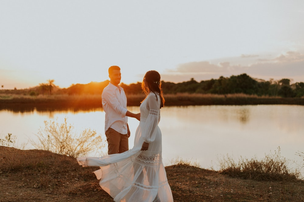 couple standing on brown grass field near body of water during daytime