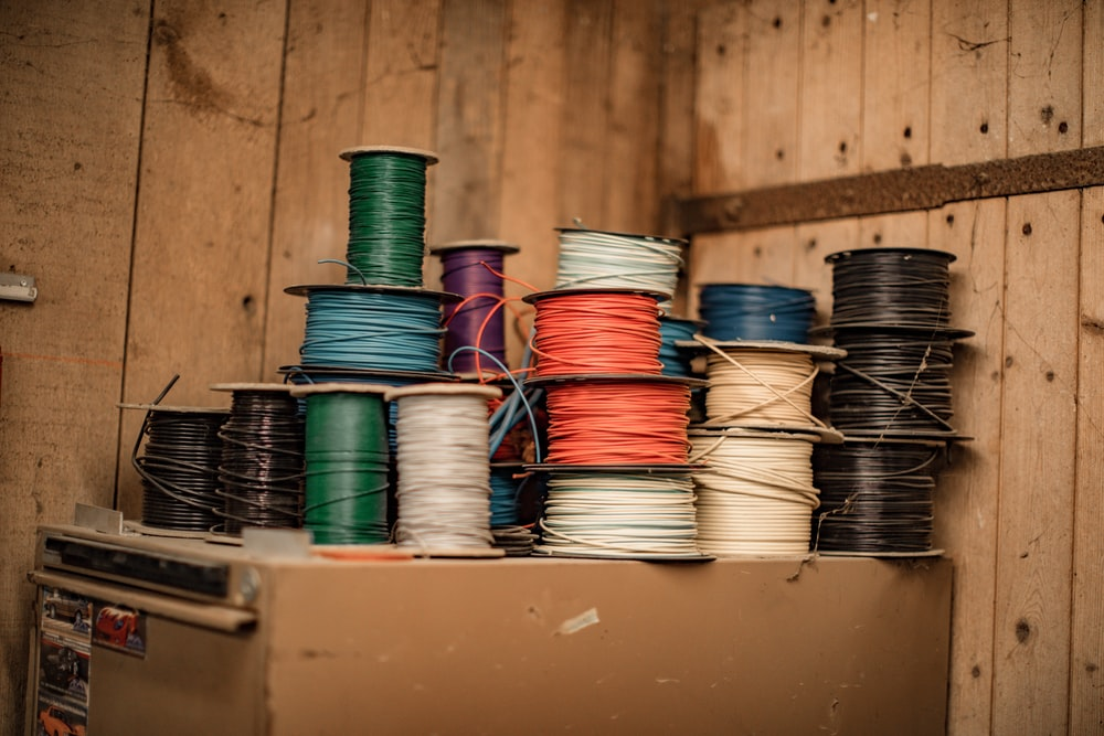blue and green thread on brown wooden shelf
