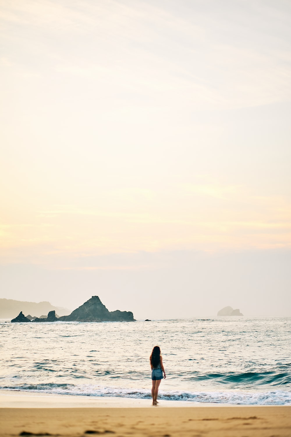 silhouette of person standing on sea shore during daytime