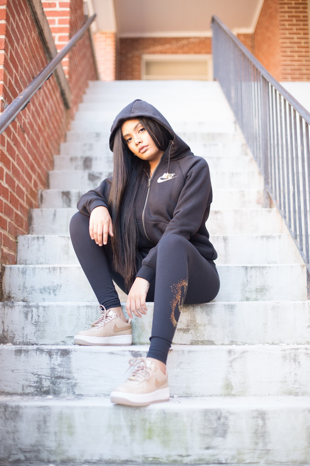 woman in black hoodie and black pants sitting on concrete stairs