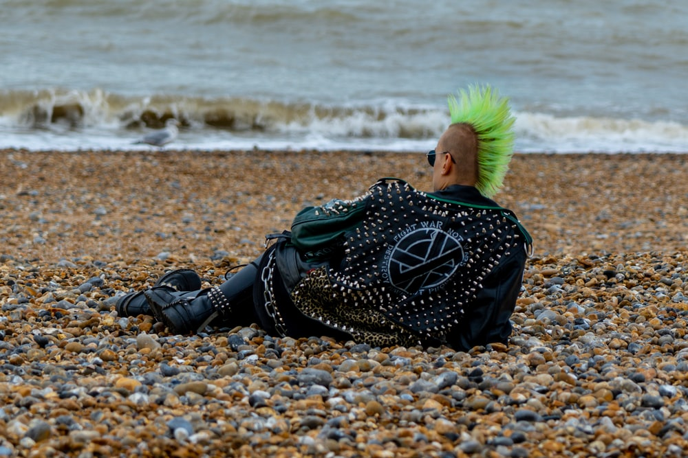 woman in black leather boots sitting on beach shore during daytime