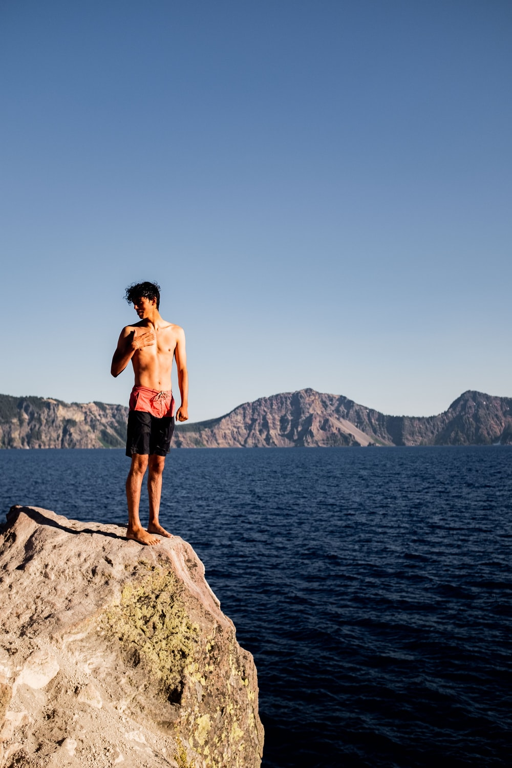 man in black shorts standing on rock formation near body of water during daytime