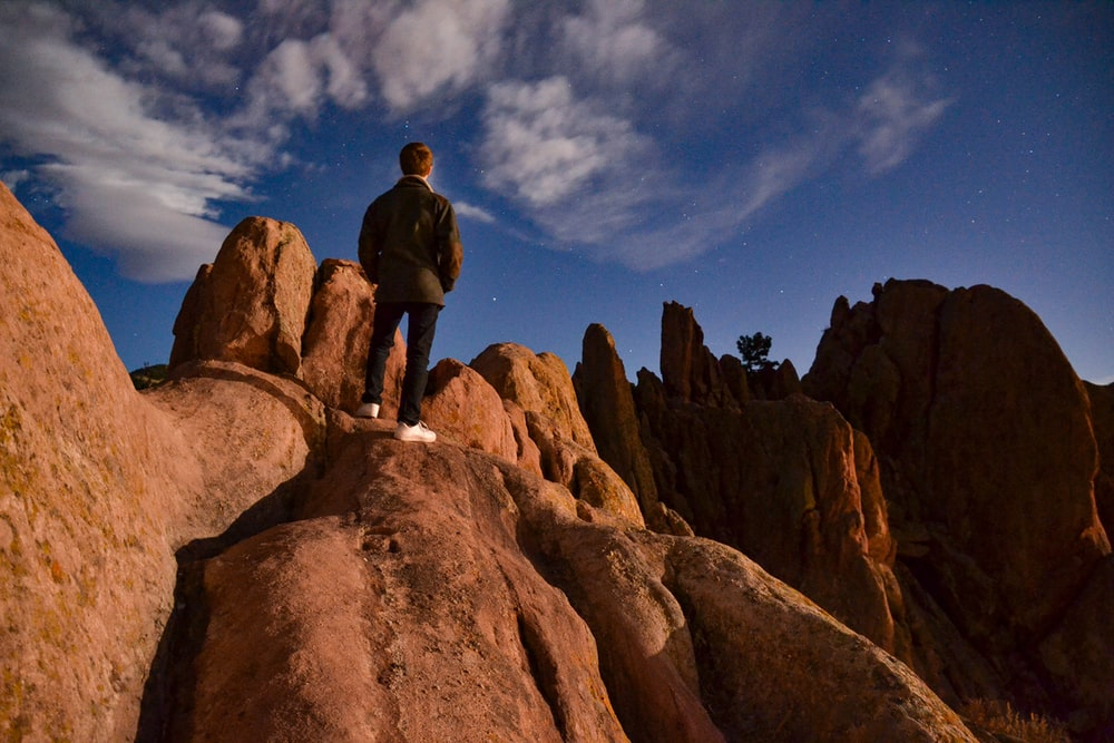 man in black jacket standing on brown rock formation under blue sky and white clouds during