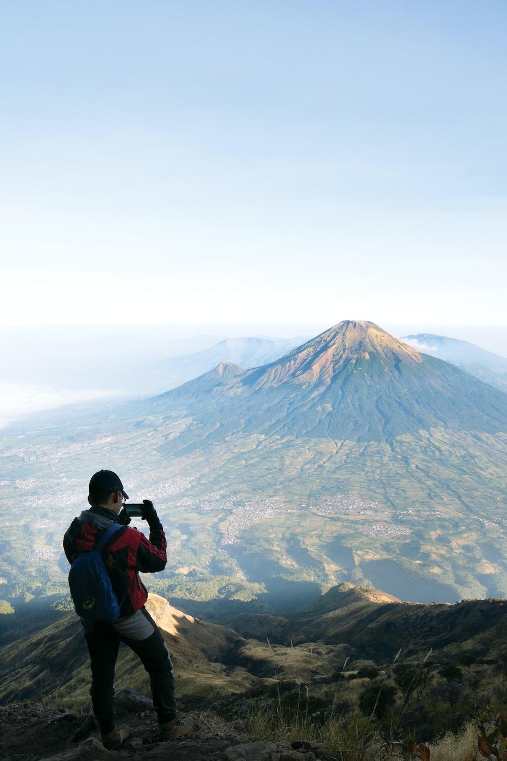 man in blue jacket taking photo of mountain during daytime