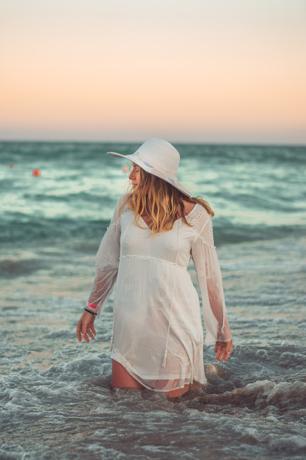 woman in white long sleeve dress standing on beach during daytime