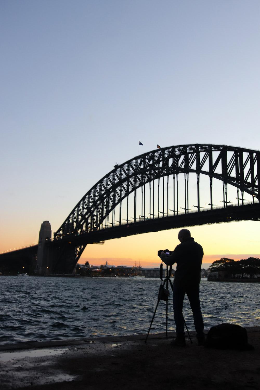 silhouette of man standing on bridge during sunset