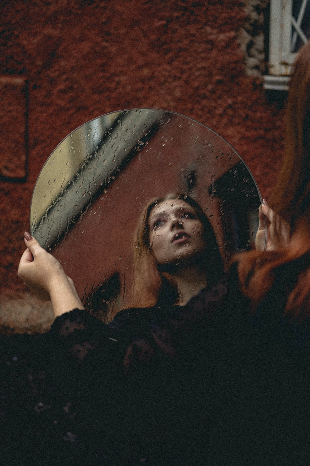 woman holding round mirror with brown wooden frame