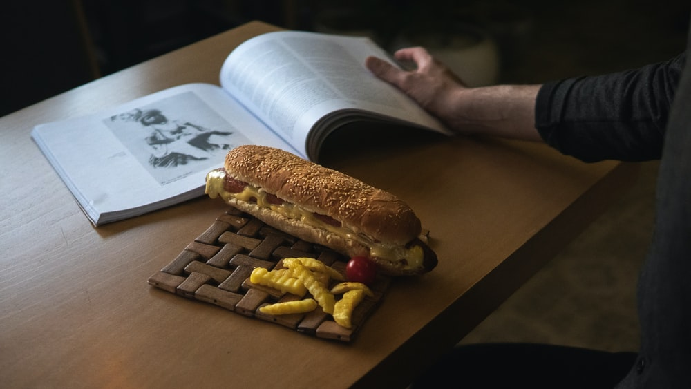 person holding bread and fries on white paper