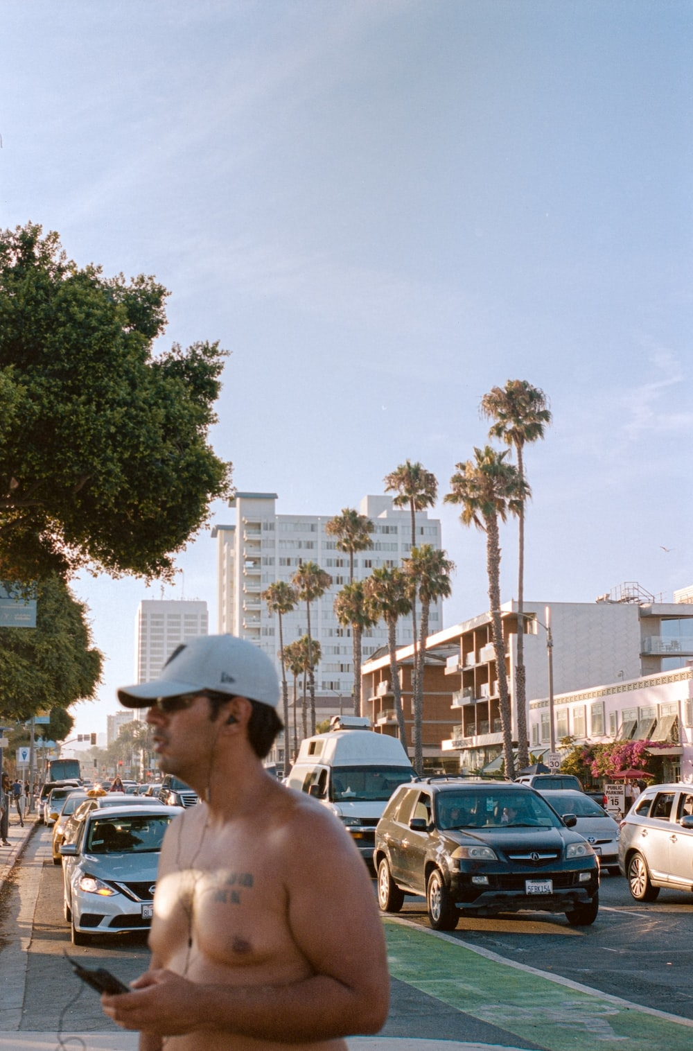 man in white hat standing near cars during daytime
