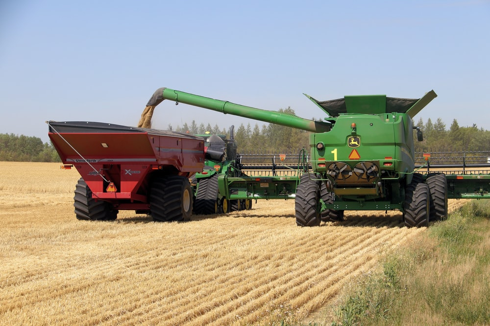 red and green heavy equipment on brown field during daytime