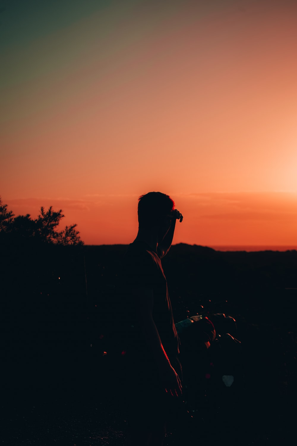silhouette of man wearing sunglasses and cap during sunset