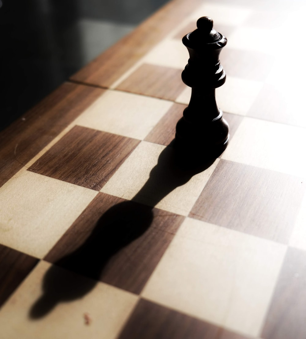 black chess piece on brown and white checkered table