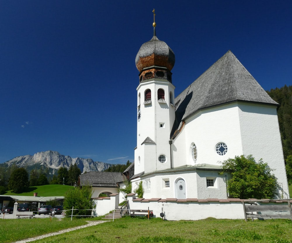 white and brown concrete church near green grass field and mountain under blue sky during daytime