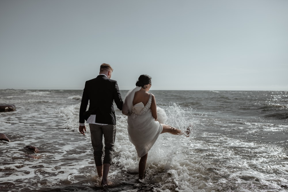 man in black suit holding woman in white dress on beach during daytime