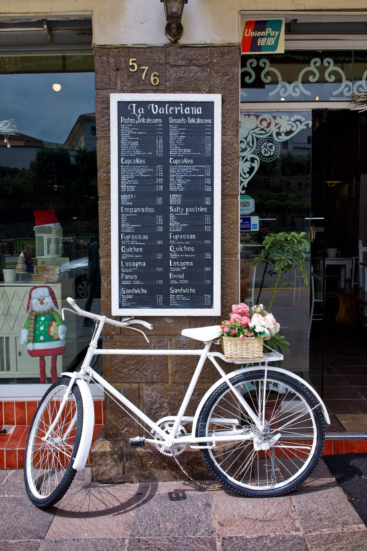 black city bike parked beside flowers