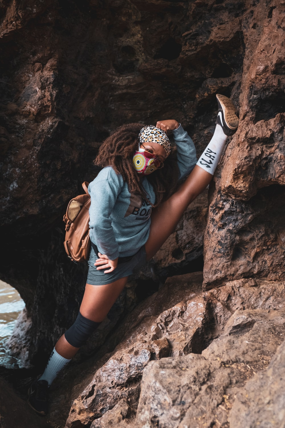 man in blue denim jacket and black shorts with brown backpack climbing on brown rock