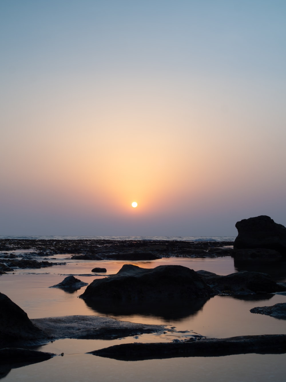 silhouette of rocks on sea shore during sunset