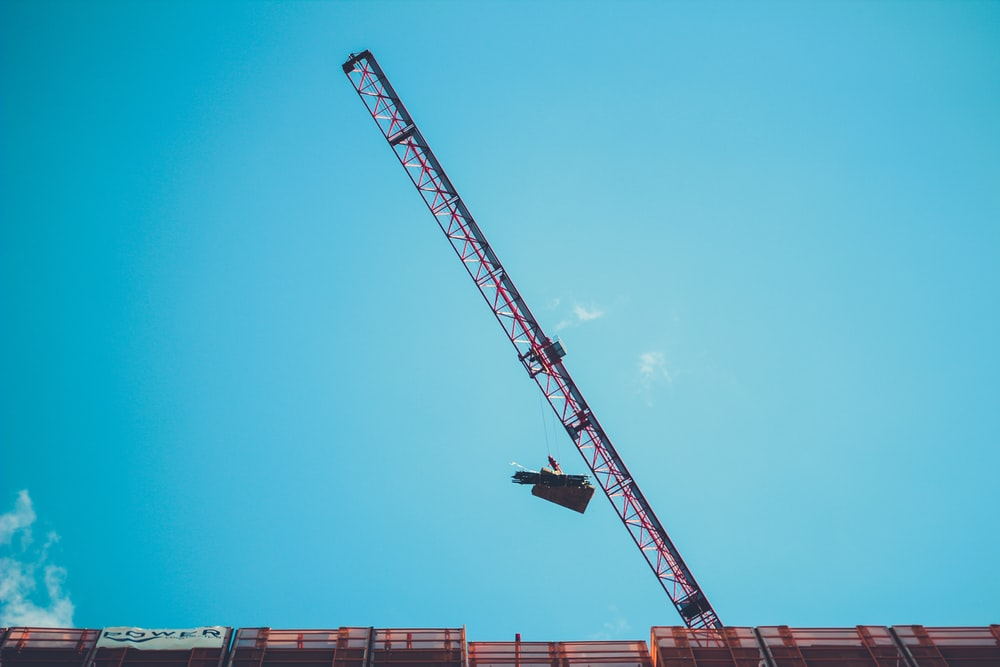 red and white crane under blue sky during daytime