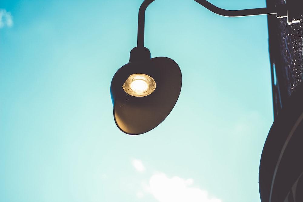 black pendant lamp turned on during daytime