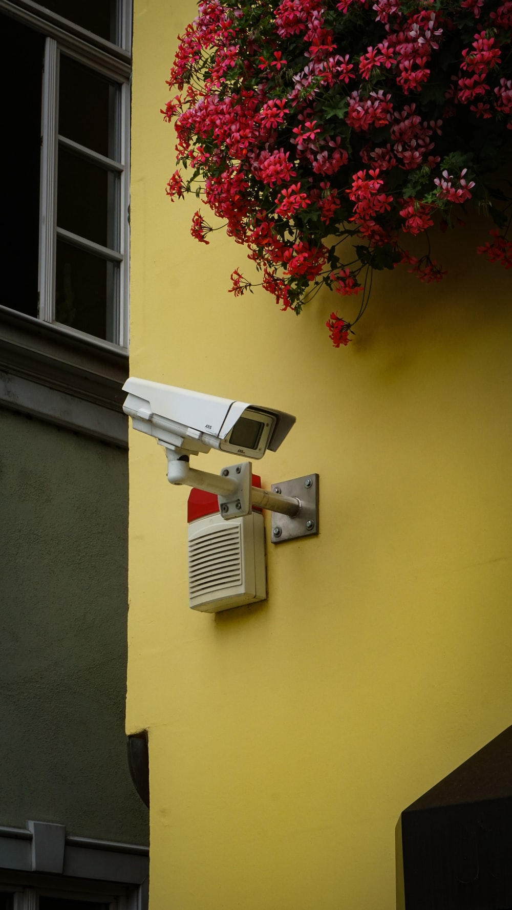 white and gray security camera mounted on yellow painted wall