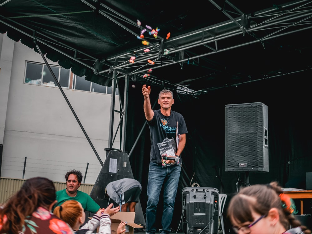 man in black crew neck t-shirt and blue denim jeans standing on stage