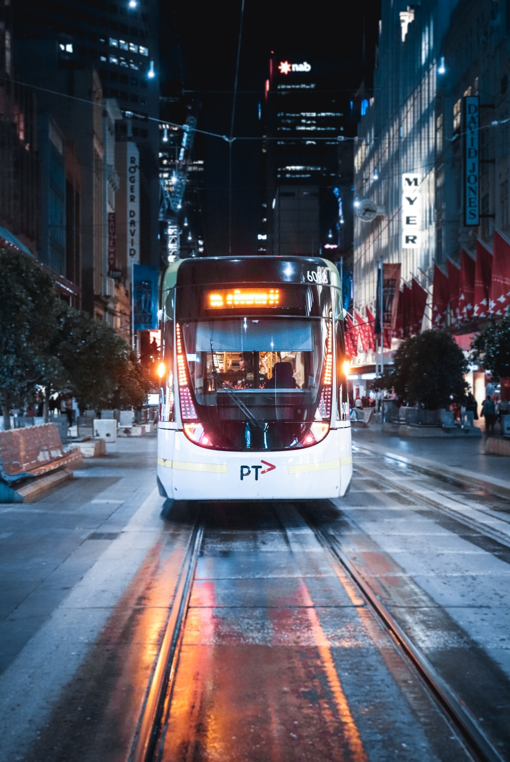 white and brown tram on road during night time