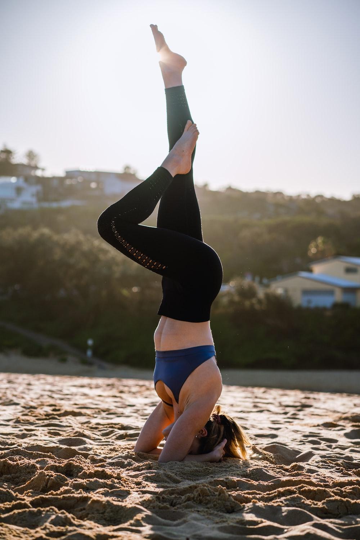 woman in black sports bra and black leggings doing yoga on beach during daytime