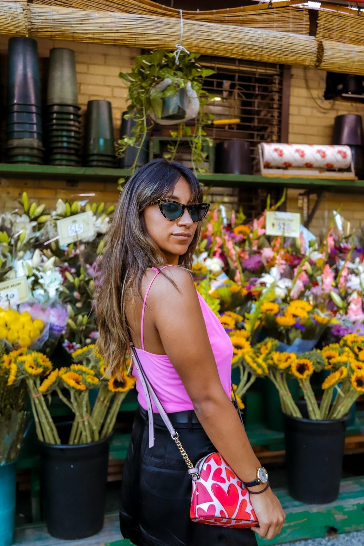 woman in pink tank top wearing black sunglasses standing near flowers