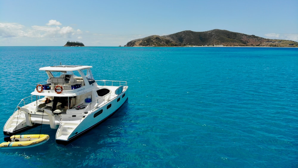 white and blue boat on blue sea during daytime