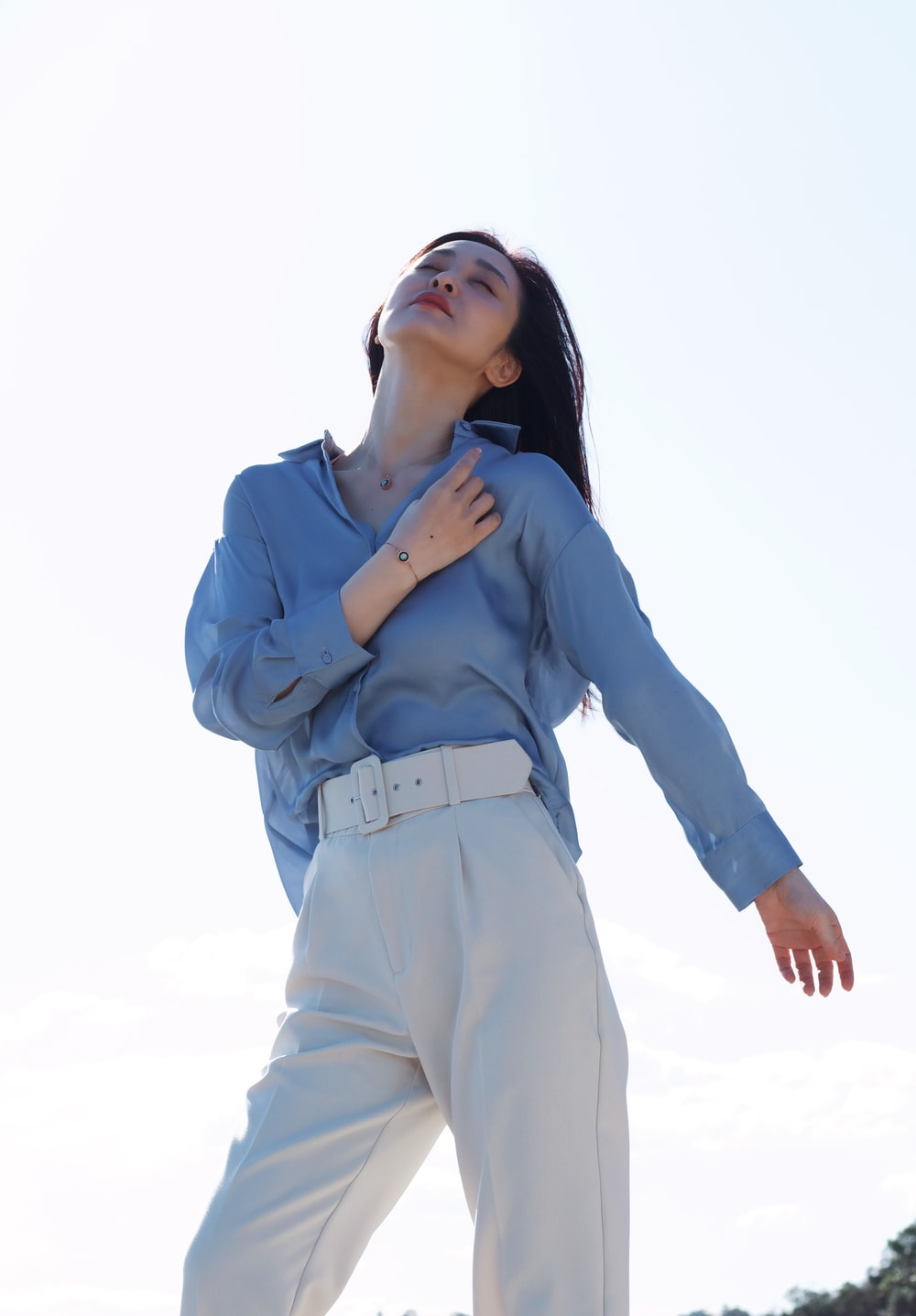 woman in blue long sleeve shirt and white pants