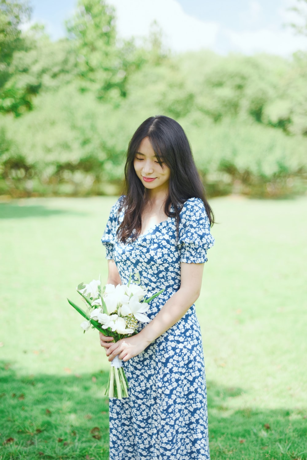 woman in blue and white floral dress holding white flower bouquet