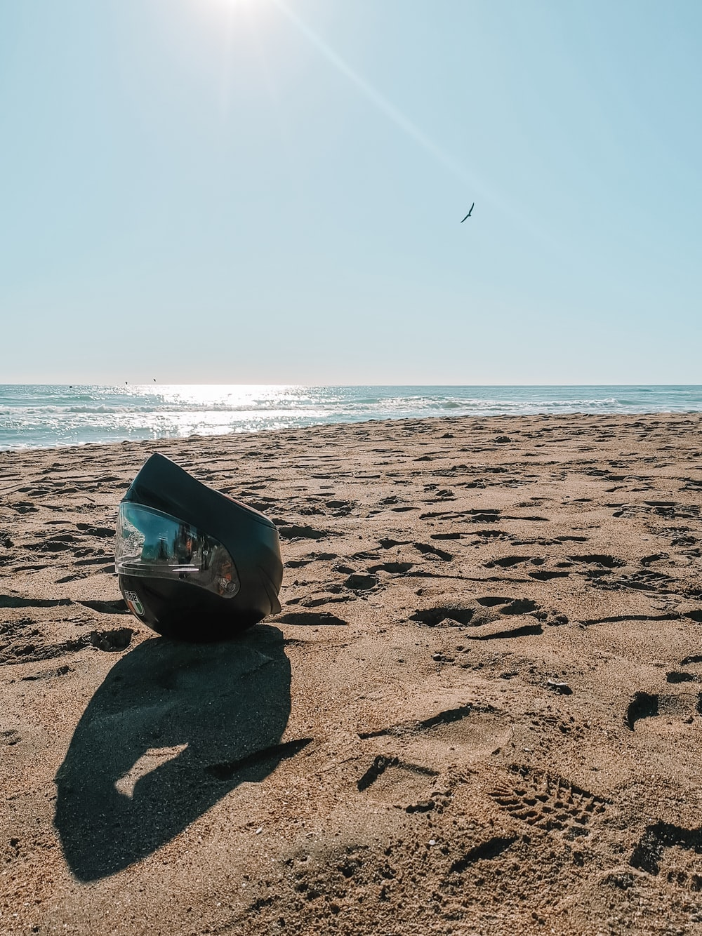 blue and white inflatable ring on brown sand near sea during daytime