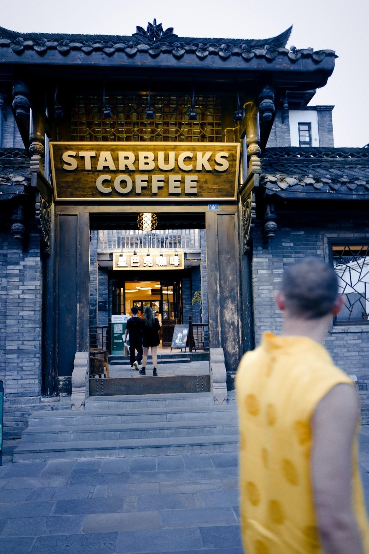 man in white t-shirt walking on sidewalk near building during daytime